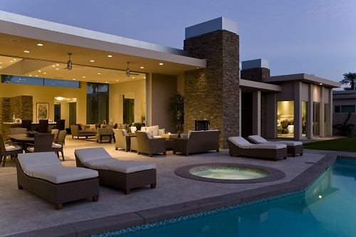 House exterior with sunloungers, recliners on patio by swimming pool
